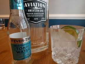 A gin and tonic beside a bottle of Aviation gin and Fever Tree Mediterranean tonic water