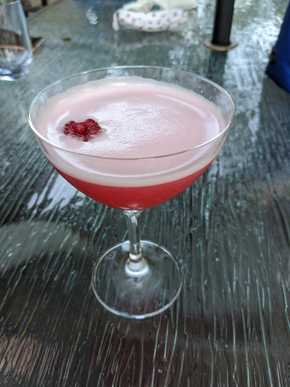 A vivid red cocktail topped with a white foam. A raspberry floats to one side atop the foam.