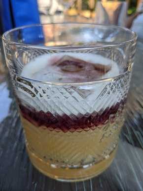 A yellow cocktail in a rocks glass deep red layer of wine floating on top.
